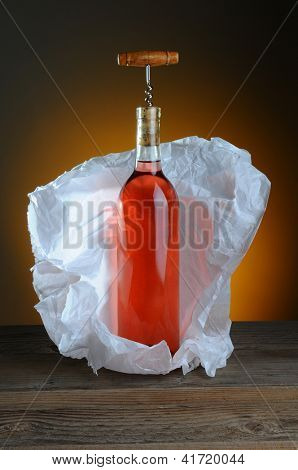 A bottle of blush wine wrapped in tissue paper, on a rustic wood surface and a light to dark warm background. A vintage cork screw is inserted in the bottle.