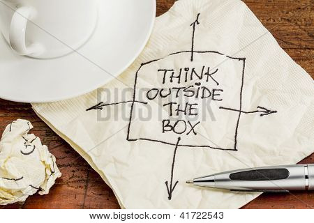 think outside the box - black pen drawing on a cocktail napkin with a coffee cup on a table