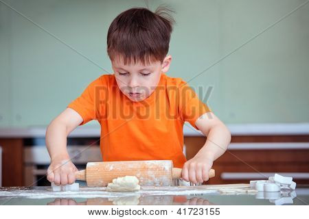 Little boy with rolling pins baking