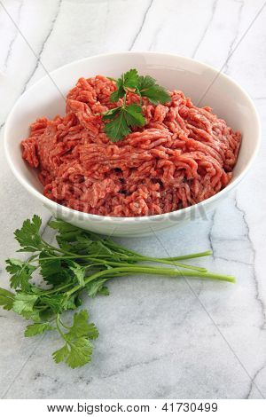 Close up of raw ground beef on marble cutting board