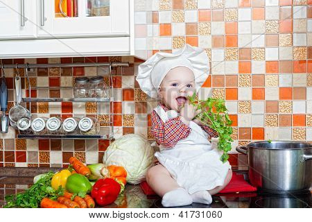 Baby cook with vegetables sits on a kitchen table