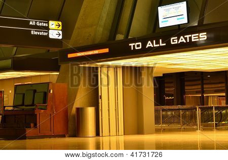 Airport interior with gates direction sign at night