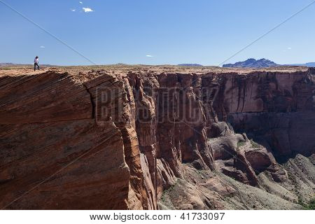 Man Looking Down A Vertical Canyon Wall