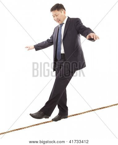 Asian businessman rope-walker. Isolated on white background