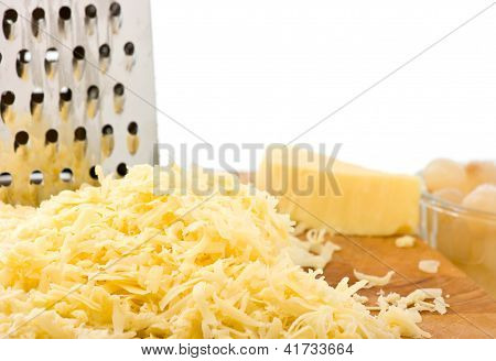Grated Cheese On Wooden Board With Grater.