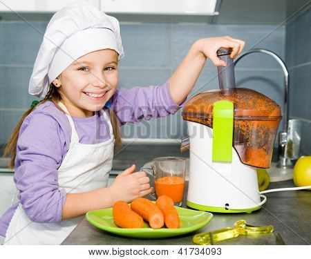 little girl making carrot juice with a juice extractor