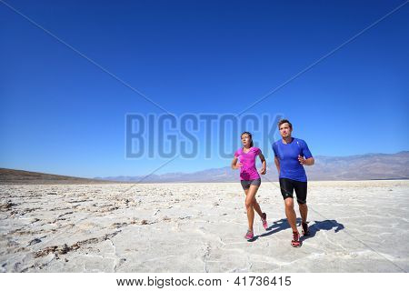Athletes running sport fitness couple outdoor. Multiracial couple of runners training outdoors in fitness clothing under burning sun in desert. Caucasian man runner and Asian woman training.