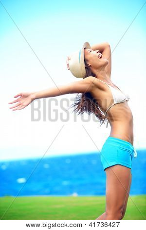 Happy freedom woman in summer standing with arms out in blissful elated happiness during summer vacation travel. Multiracial asian caucasian fashion hipster wearing hat outdoor.