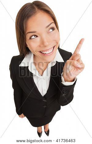 Business woman pointing showing and looking to the side up at empty copyspace. Multi ethnic Asian Chinese / Caucasian female businesswoman standing isolated on white background in full body length.