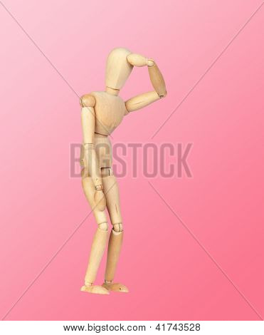 Jointed wooden mannequin representing discouragement isolated on a pink background