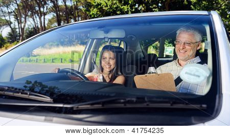 Learner driver student driving car with instructor. happy and confident smiling girl