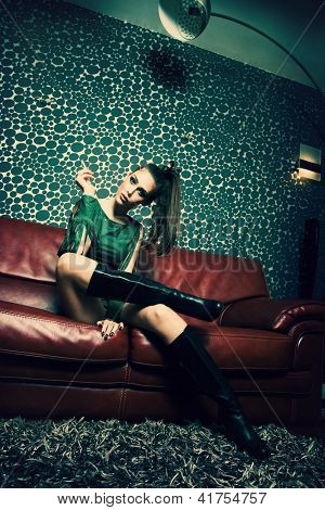 attractive young woman in green dress and long boots sit and smoke in retro style living room