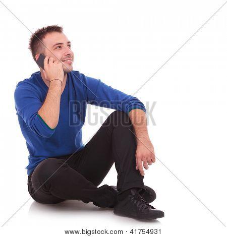 joven casual hablar por teléfono mientras tendido en el suelo - mirando lejos de la cámara