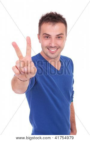 young casual man making victory hand gesture and smiling on white background