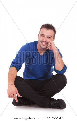 young casual pensive man sitting with legs crossed and holding his head while smiling to the camera. isolated on white