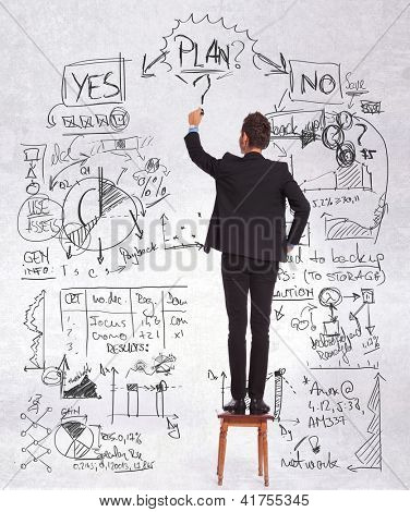 back of a business man standing on a chair and drawing a sketch of a presentation