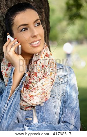 Attractive young woman using mobile phone in park, looking away.