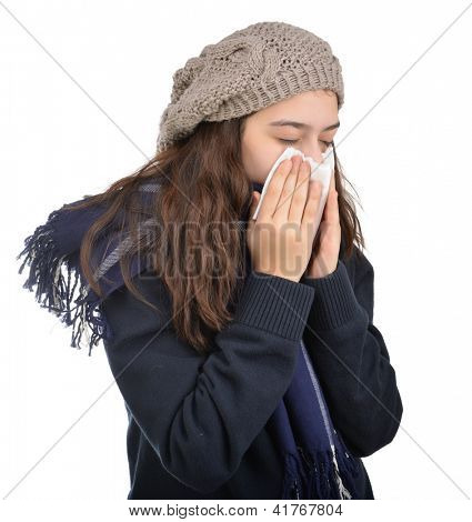 Teenager sneezing into a tissue isolated on white background
