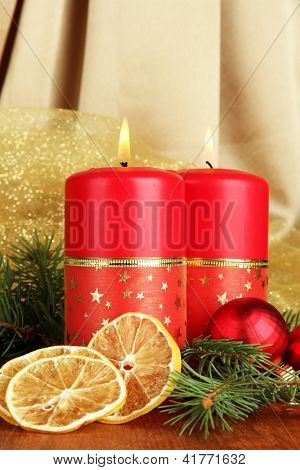 Two candles and christmas decorations, on golden cloth background