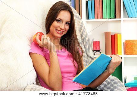 Retrato de mujer comer manzana y libro de lectura en casa