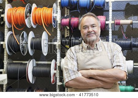 Portrait of a happy middle-aged salesperson standing in front of electrical wire spool with arms crossed in hardware store