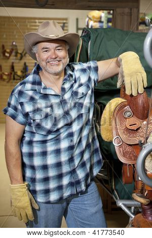 Portrait of a happy middle-aged cowboy standing by saddle in feed store