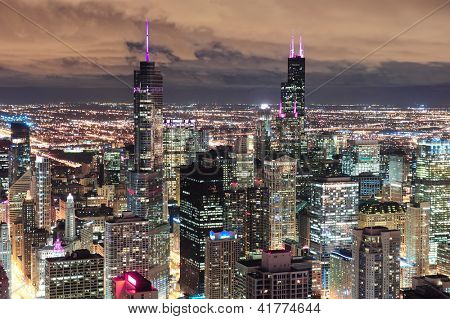 Chicago urban skyline panorama aerial view with skyscrapers and cloudy sky at dusk with lights.