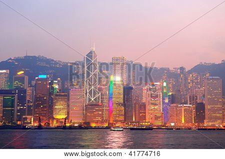 Mañana puerto Victoria de Hong Kong con rascacielos urbanos sobre mar iluminado con reflejos.