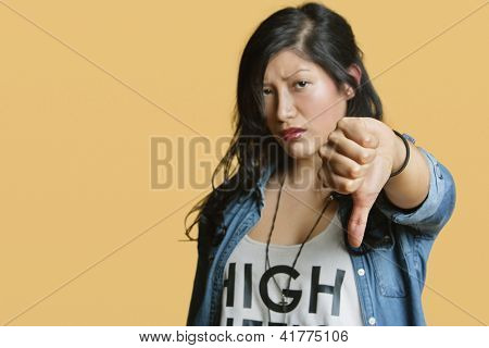 Portrait of a young woman showing thumbs down over colored background