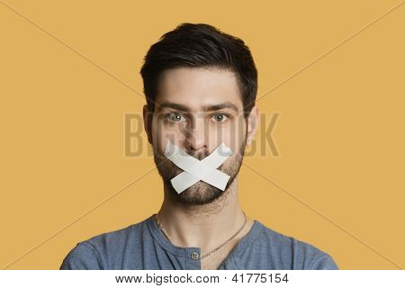 Portrait of a young man with tape on mouth over colored background