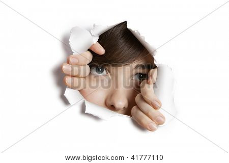 Middle eastern woman peeking from ripped white paper hole