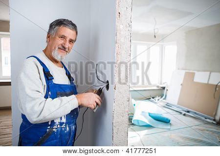 Senior man working on the electrical installations in a freshly renovated appartment