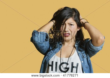 Portrait of a frustrated young woman with hands in hair over colored background