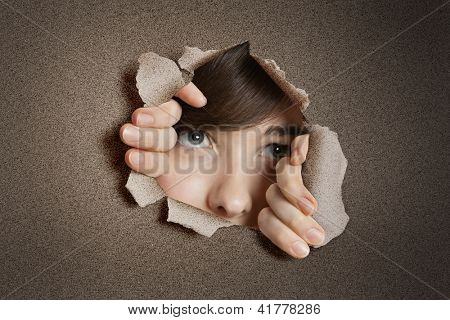 Young woman peeking from ripped white paper hole