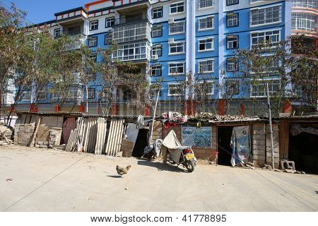 KUNMING - DECEMBER 20: Modern high-rise buildings encroach on old farm quarters seen outside KunMing, China on December 20, 2013. A vibrant economy brings development to even rural areas of China.