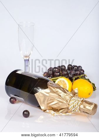 recumbent bottle of champagne and fruits