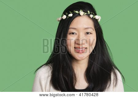 Portrait of a beautiful young woman wearing a hair wreath over green background