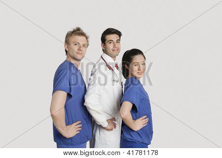 Retrato da equipe médica permanente de mãos nos quadris, sobre fundo cinza