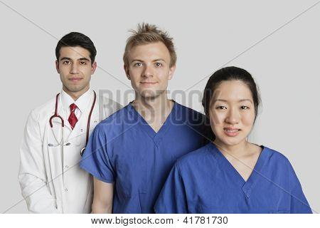 Retrato de pé diversificada equipe médica sobre fundo cinza