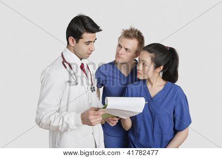 Profissionais de saúde étnicas multi, discutindo o relatório médico sobre fundo cinza