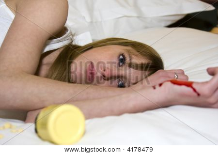 Young Female Attempting Suicide With Pills And Cutting Arm