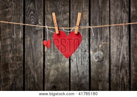 Two lovely red hearts - big and small hanging on the clothesline. On old wood background with a lot of copy space.