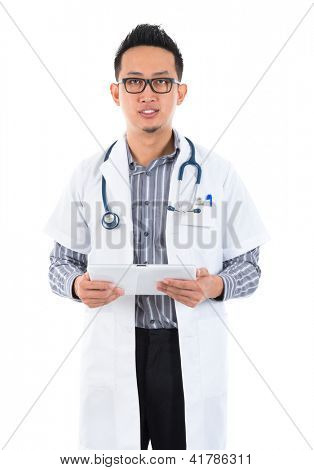Southeast Asian medical doctor. Serious male medical doctor holding a tablet computer standing on white background.