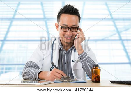 Young Southeast Asian medical doctor writing a note while calling on the phone, sitting in front a desk inside hospital.