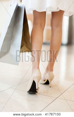 rear view of young woman walking with shopping bags