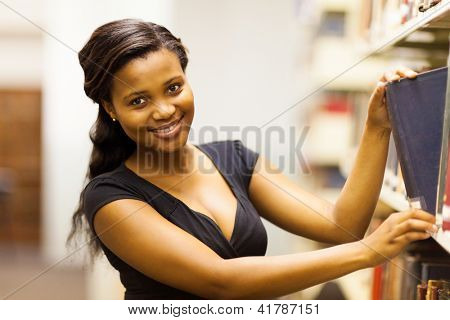 happy african american college girl looking for book in library