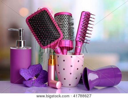 Hair brushes, hairdryer and cosmetic bottles in beauty salon