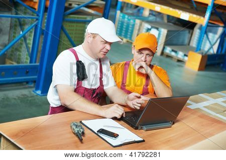 two young handsome workers man in uniform in front of warehouse rack arrangement stillages using notebook laptop computer