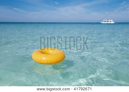 floating ring on blue clear sea with white boat, shallow dof