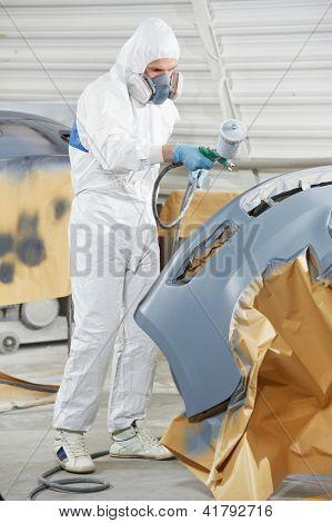 auto tope del coche de pintura trabajador mecánico en reparación de automóviles y renovar la tienda de la estación de servicio por spra